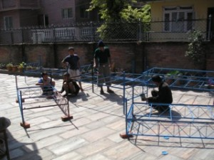 The bed frames being assembled in the front yard