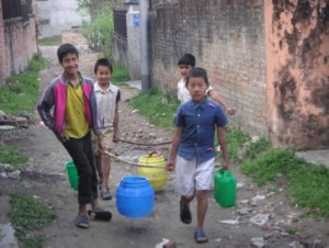 Some of the older boys carrying water to the Home
