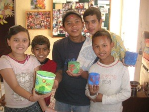 The children showing off the pape mache pots they made in school